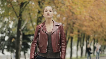 модный : Autumn is coming. Elegant woman in burgundy leather jacket walk in city street, slowmotion.