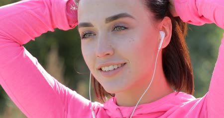 knotted : Close up of smiling sportswoman tying her hair before jogging Stock Footage