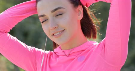 knotted : Close up of smiling sportswoman tying hair before jogging
