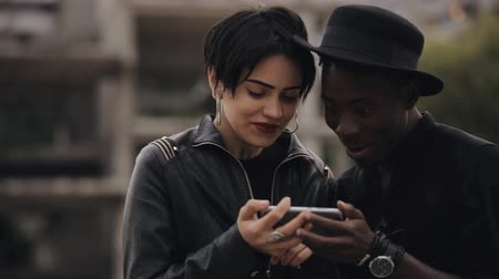 nevetséges : Slowmotion of white woman and black man couple looking down to video on smartphone. They laughing together, video is very ridiculous.