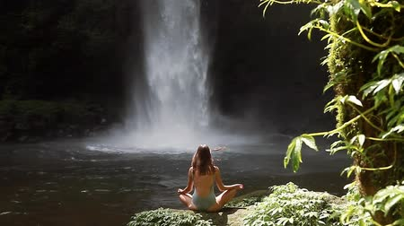 poça de água : girl meditating in front of waterfall