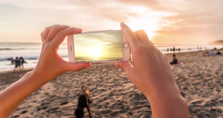 sinematografi : Womens hands takes a sunset on a smartphone in the evening on the beach in cinemagraph style with timelapse