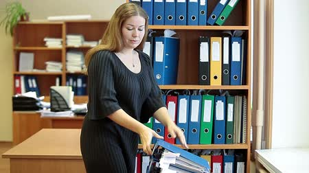 arquivos : Video of a young attractive businesswoman with folders standing before bookshelves