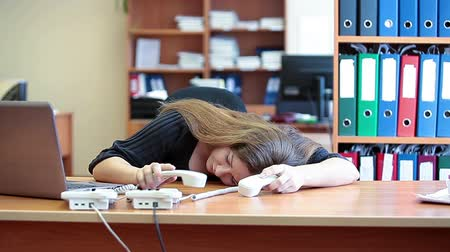 усталый : Young tired business female sleeping on the keyboard at work and trying to speak on the phones Стоковые видеозаписи