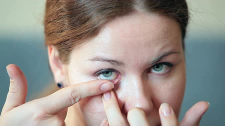 kontakt : Young Caucasian woman inserting clear contact lens in her eye