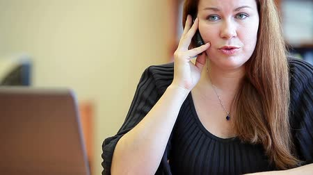 dialog : Close up of beautiful Caucasian female speaking on the cellphone in office