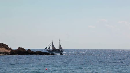 парусный спорт : Two-masted sail ship sailing on the Mediterranean sea over rocky island, Cyprus