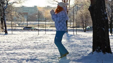 csak a fiatal nők : Frozen woman jumping in winter park against sunshine