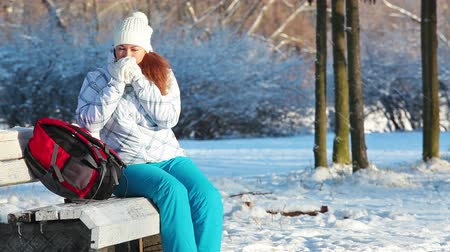 zmrazit : Woman with frozen hands sitting on the park bench in winter season, Russia