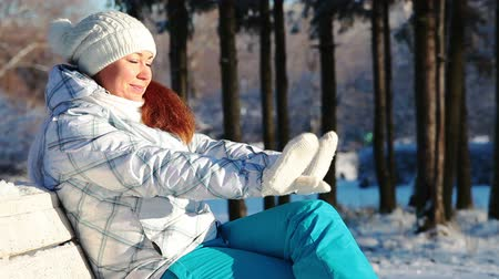 mittens : Woman sitting on the bench and covering face by hands from sun light. Winter season Stock Footage