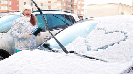 cleaning equipment : Pretty woman brushing windshield with drawing heart shape on snow. Winter season. Russia