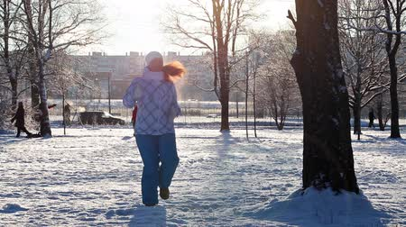 cold : Woman making exercises in wintry city park against sunlights, cold weather, Russia