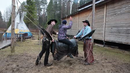 býci : Young woman screaming when riding on bull simulator with two cowboys, Russia