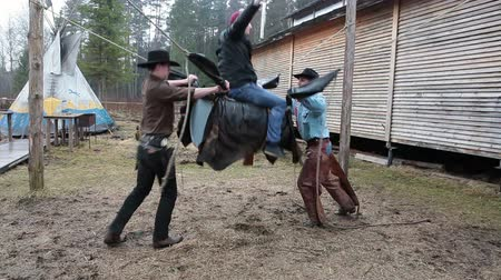 býci : Teenage man bullriding on handy bull simulator with two cowboys, Russia