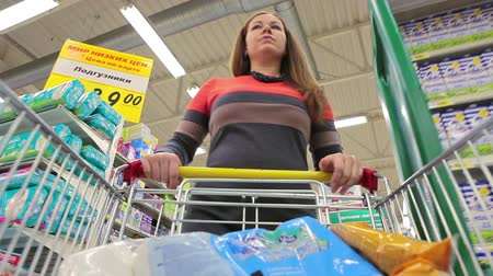 kordé : Young woman adding goods with shopping cart in wholesale market Stock mozgókép
