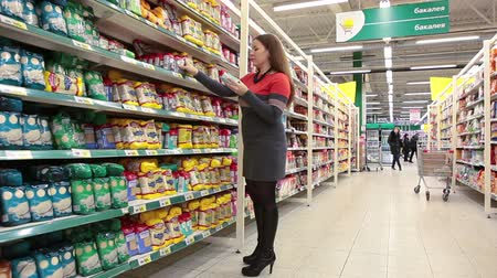 áruk : Young woman in shopping center choosing goods, Russian wholesale market