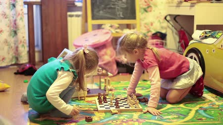 sitting room : Pretty girls playing chess on the floor of nursery Stock Footage