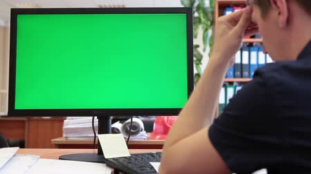 рабочих мест : Engineer worker thinking and looking at green scree of pc, chromakey, big monitor