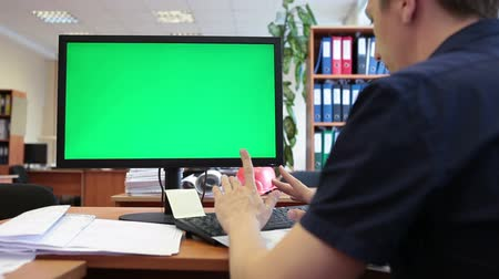 komputer : Caucasian worker typing on keyboard and looking at green screen
