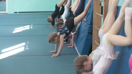 gimnastyka : Children making handstand position on acrobatic lessons on the floor, Russian sports school for preschoolers