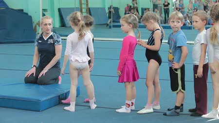gimnastyka : Young kids standing in queue for making roll over at acrobatic exercises. Children sport school of Olympic reserve in Saint-Petersburg