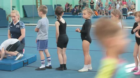 gimnastyka : Preschool kids making roll over at acrobatic exercises. Children sport school of Olympic reserve in Saint-Petersburg