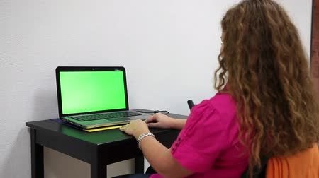 онлайн : Pretty woman starting online chat with friend, green screen laptop on the desk