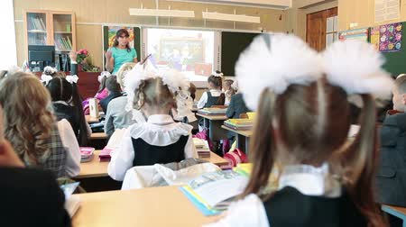 initial : Rear view of first grade students on lesson in school. September, 1 in Russia