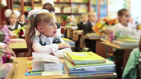 элементарный : Beautiful girl first grader sitting at the desk in classroom in school. September, 1 in Russia