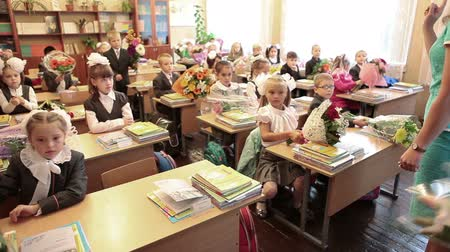 initial : First-form kids with flowers are in the classroom at first lesson in school. September, 1 in Russia