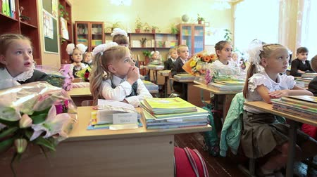 birincil : First-form girls sitting at the desks at first lesson in school. September, 1 in Russia