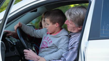 new car : Father and mother showing son a new just buying car sitting inside Stock Footage