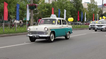 stare miasto : KOLPINO, SAINT-PETERSBURG, RUSSIA -CIRCA SEPTEMBER, 2014: Parade is on the town streets dedicated Kolpino town anniversary. Old taxi car is on the head of procession Wideo