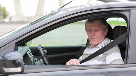 přezka : Senior male sitting in car and fastens seat belt