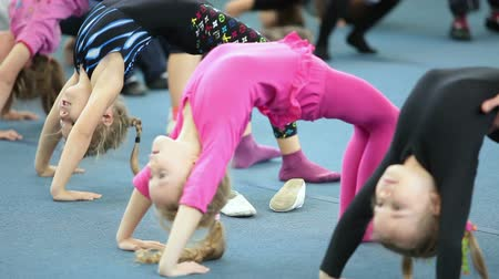gimnastyka : Girls make a bridge in the gym. Open lesson in acrobatics school for preschool children in Saint-Petersburg, Russia Wideo