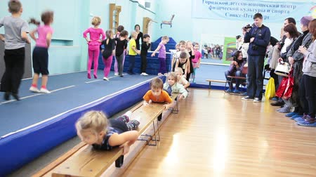 gimnastyka : SAINT-PETERSBURG, RUSSIA - CIRCA MAY, 2013: The open lesson in gymnastics for preschoolers in Russian sport school, Russia. Kids make exercises when parents watch they