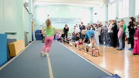 gimnastyka : SAINT-PETERSBURG, RUSSIA - CIRCA MAY, 2013: The open lesson in gymnastics for preschoolers in Russian sport school, Russia. Kids jump on sport runway at the open lesson with watching parents
