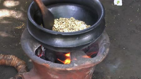 cooking pots : Roasting raw coffee beans in pan for beverage preparing. Arusha coffee plantation, Tanzania, Africa. Process of making coffee