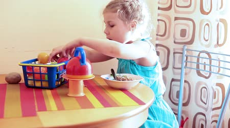 gruel : Child in blue dress eating gruel at the table and playing with her toys