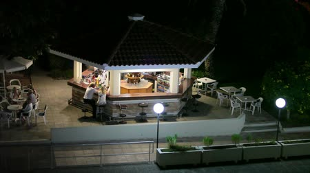буфет : Hotel area at night with resting drinking mature people sitting in bar
