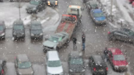 evacuated : Defocused view of tow truck takeing broken car from the parking lot. Heavy snow. Saint-Petersburg, Russia Stock Footage