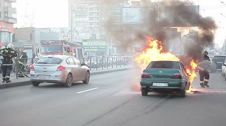 firemen : Firefighters arrived to extinguish inflaming car on a city street Stock Footage