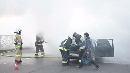 firemen : Firefighters in clouds of smoke from a burning car and owner, helping to open the trunk. Accident with fire on city street