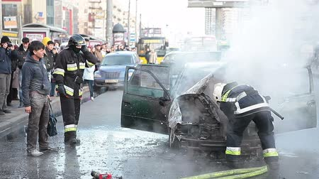 fire officer : Owner of the burnt car coming to firefighters after extinguishing. Accident on sity street, Russia Stock Footage