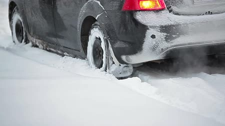 toló : The car stalled on a snowy road and people kicking him out of a snowdrift Stock mozgókép