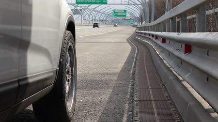 high speed road : Side view of front wheel of vehicle standing on highway curb Stock Footage