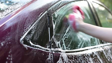 sünger : Foam on the car windows and female hand with sponge washing vehicle Stok Video
