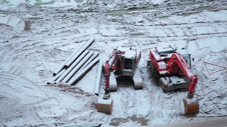 épít : Two tip lorries and excavators parking on construction site in winter season, Russia