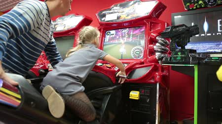 vending machine : Small girl riding a simulated motorcycle with father help. Children game zone. Russia Stock Footage