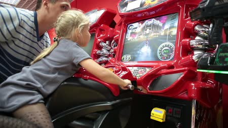 vending machine : Young girl playing video arcade game. Motorcycle simulator racing machine. Father helping daughter
